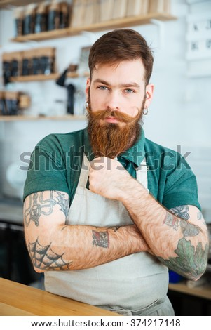 Attractive male barista with tattooed hands standing in coffee shop and touching his beard - stock photo