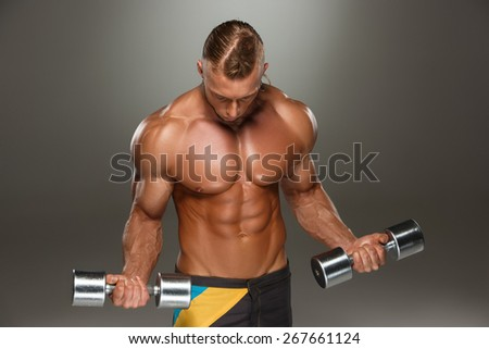 Attractive male body builder with dumbbells on gray background. - stock photo