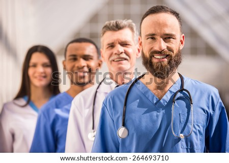Attractive male doctor in front of medical group in  hospital. - stock photo