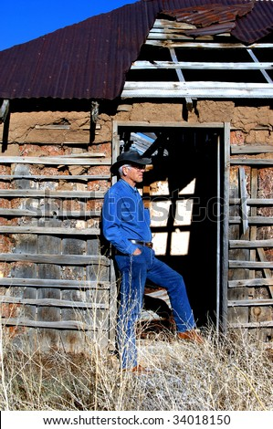 Attractive male, dressed in denim and boots, leans against the door jam of an old adobe home outside of Alberquerque, New Mexico. - stock photo