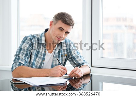 Attractive male in checkered shirt sitting and working in the office - stock photo