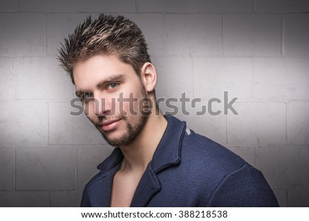 Attractive male model and handsome young man. Fashionable hunk wearing a blue jacket, blazer against a white brick wall. - stock photo