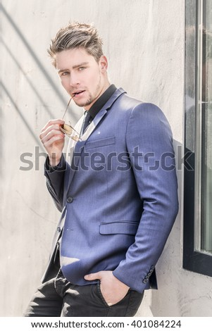 Attractive male model wearing a blue suit - Summertime - Young stylish confident young man - stock photo