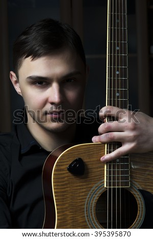 Attractive male musician with acoustic guitar - stock photo