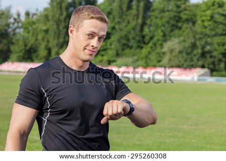 Attractive male runner is checking his results and looking at his watch. He is smiling at the camera with satisfaction. There is copy space in right side - stock photo