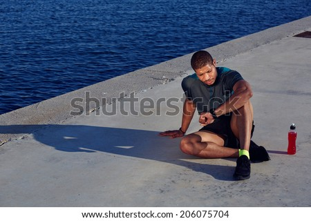 Attractive male runner looking at smart watch having rest after jogging outdoors, healthy african american man resting tired after evening training seated in the sea port at sunset, fitness concept - stock photo