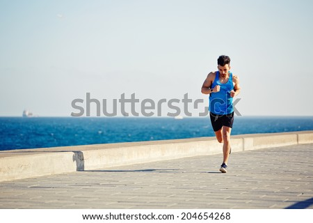 Attractive male runner with muscular strong body runs along the pier on a beautiful sea background, fitness and healthy lifestyle concept - stock photo