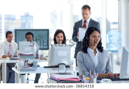 Attractive male supervisor taking notes in a call center