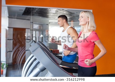 Attractive man and woman are running on treadmill in fitness center. They are looking forward and smiling