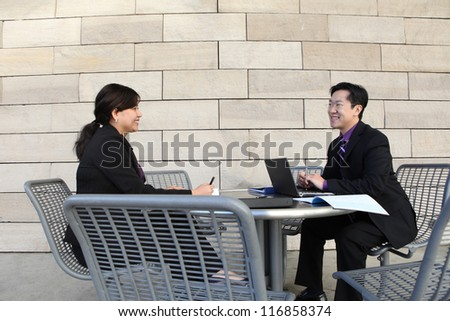 Attractive man and woman Chinese business couple working on laptop computer - stock photo