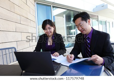 Attractive man and woman Chinese business team working on laptop computer