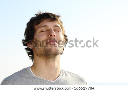 Attractive man breathing outdoor with the sky in the background              - stock photo