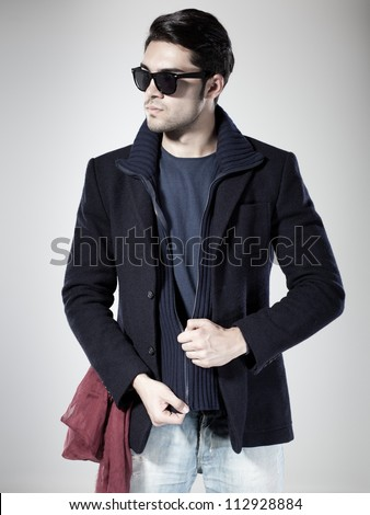 attractive  man dressed casual with sun-glasses posing in the studio - stock photo