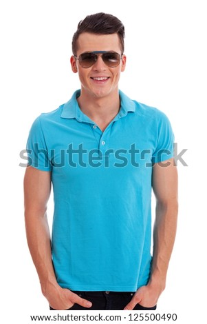 attractive man dressed casually in a polo shirt standing with hands in his pockets, wearing sunglasses, on white background - stock photo