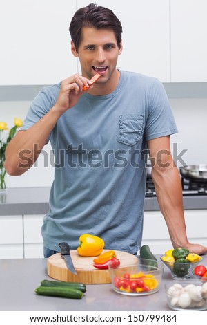 Attractive man eating a slice of bell pepper in the kitchen - stock photo