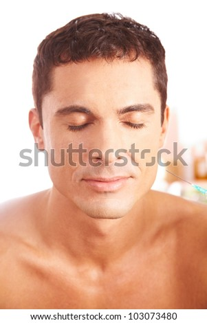 Attractive man getting treatment with syringe in beauty clinic - stock photo