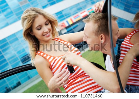 Attractive man giving keys of new car to his girlfriend - stock photo