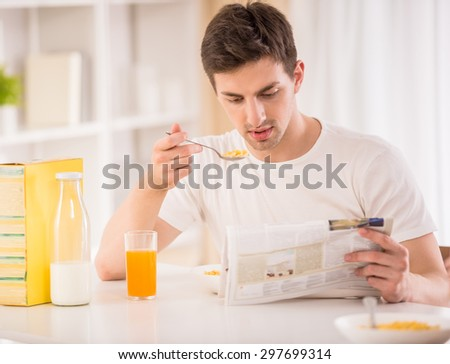Attractive man having breakfast and reading newspaper in the kitchen.