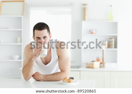 Attractive man having breakfast in his kitchen