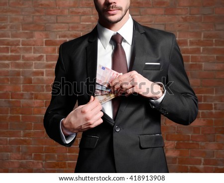 Attractive man hiding euro banknotes in suit on brick wall background - stock photo