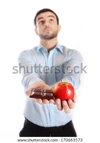 Attractive man holding Chocolate and Apple as a diet choice isolated on White background, a decision for a healthy life and lose weight