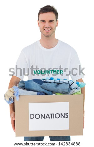 Attractive man holding donation box with clothes on white background - stock photo