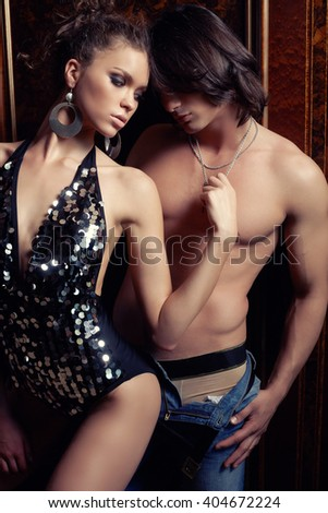 Attractive man holds in his arms awesome sexy woman in a glitter dress