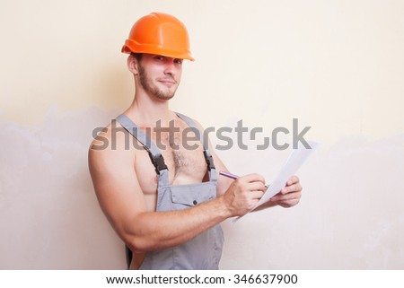 Attractive man in a helmet writes on paper - stock photo