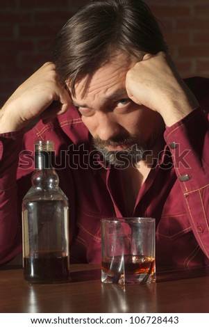 Attractive man in a red shirt with alcohol