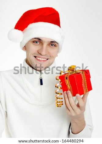 Attractive man in a Santa hat with Christmas gift