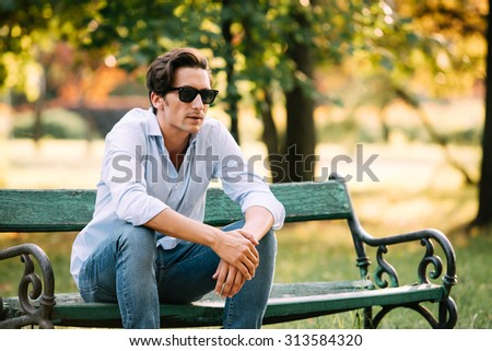 attractive man in blue shirt sitting alone on the bench in park with cellphone and sunglasses