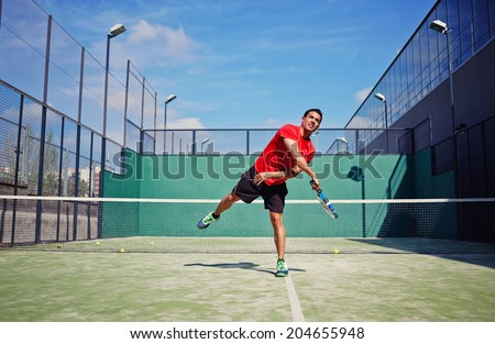 Attractive man in bright sportswear with racket in the hands feed ball in paddle game, paddle game outside, healthy lifestyle concept