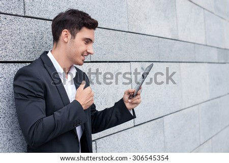 Attractive man in suit is holding a tablet and standing near building. He is looking at it with joy and smiling. The worker is giving thumb up. Copy space in right side - stock photo