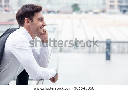 Attractive man in suit is standing and holding his jacket behind his back. He is leaning on border of building and smiling. The man is talking on telephone with enjoyment. Copy space in right side - stock photo