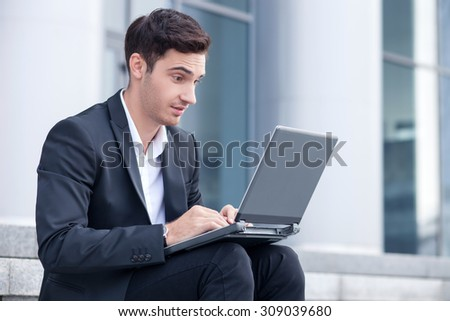 Attractive man in suit is using a laptop for work. He is sitting on steps. The man is looking at the technology with surprise. The news shocked him - stock photo