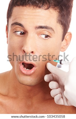 Attractive man is afraid of a needle and syringe - stock photo