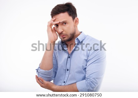 Attractive man is covering his face with his hand with shame. He has depression and hopelessness. Isolated on a white background - stock photo