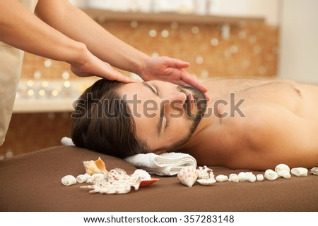 Attractive man is getting head massage at beauty salon. He is resting and lying. The man closed his eyes with enjoyment - stock photo