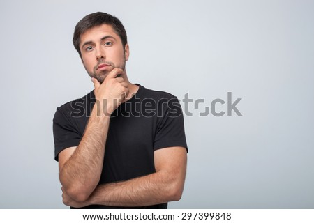 Attractive man is looking at the camera pensively. He is thinking about his future. The man is touching his chin with seriousness. Isolated on grey background and copy space in right side - stock photo