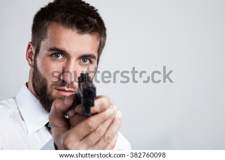 Attractive man is pointing with a gun at you - stock photo
