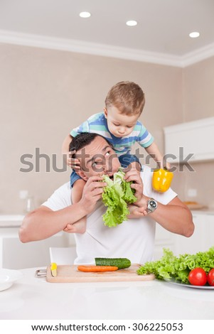Attractive man is sitting at the table and holding his son on his shoulders. He is touching leaves of lettuce to his chin and smiling. The boy is looking at parent with interest and holding a pepper