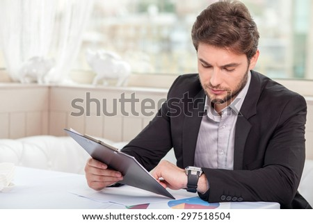 Attractive man is sitting at the table and is working on his project. He is holding a folder with documents in his hand. The man is looking at his watch attentively. Copy space in left side - stock photo
