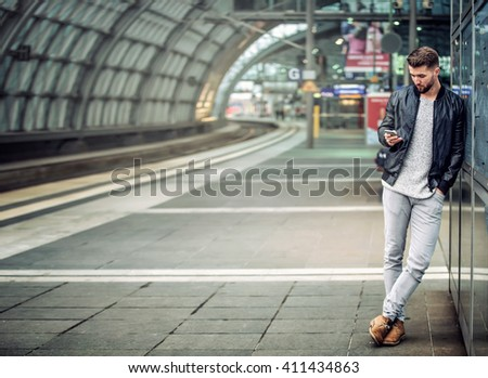 Attractive man is waiting at the train station looking at his smart phone