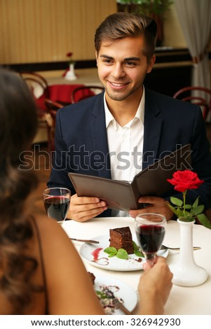 attractive man keeps eye on his wife at the restaurant - stock photo