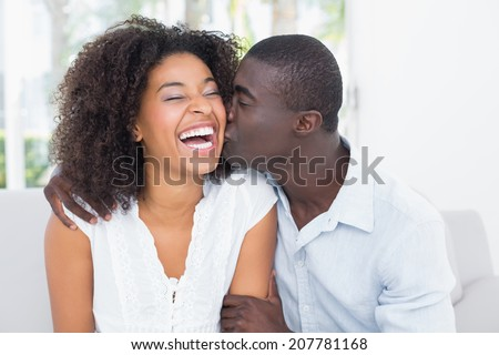 Attractive man kissing his girlfriend on the cheek at home in the living room - stock photo