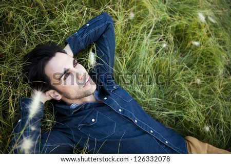 Attractive man lying in the grass wearing a blue jeans shirt. - stock photo