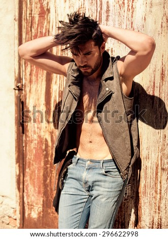 attractive man model dressed punk, hipster posing dramatic in grunge location - stock photo