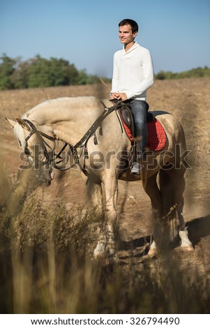 Attractive man on horseback, - stock photo