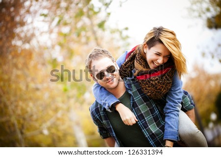 Attractive man piggybacking his pretty girlfriend outdoors - stock photo