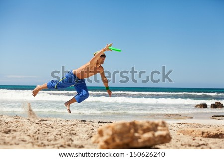 attractive man playing frisby on beach in summer sport fitness jump - stock photo